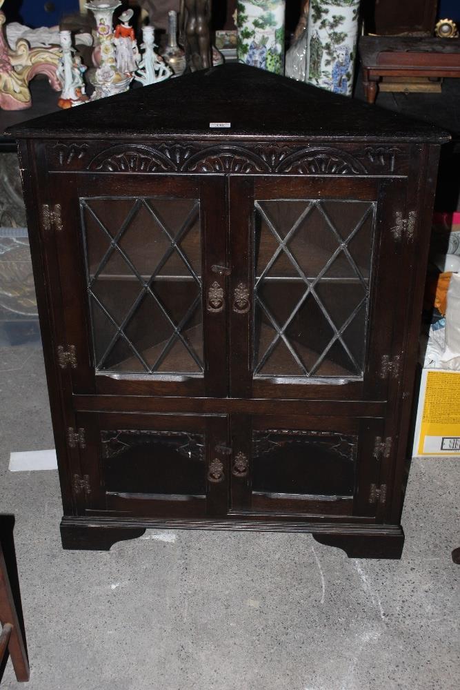 A stained oak glazed corner cupboard, in