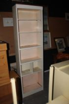 A tall slender white painted bookcase, w