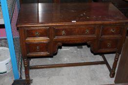 A 1920's oak knee hole writing desk, wit