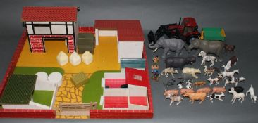 A wooden toy farm yard with accessories, a Britain's diecast tractor with trailer,