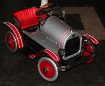 A Syot imitation delux Model T Ford Roadster pedal car in red and silver,
