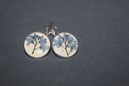 A pair of white metal earrings,