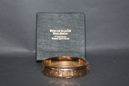An early 20th century rose gold plated hinged bangle with engraved top and metal core. 6.