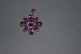 A 9ct gold and amethyst floral pattern pendant set with 9 cut stones of oval and pear shape, 3.
