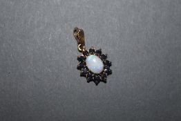 A 9ct gold opal and blue stone (Thought Sapphire) oval pendant the central cabochon opal surrounded
