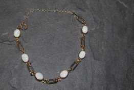 A 9ct gold and opal bracelet the six oval opals in dispersed by rectangular links,