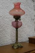 Antique oil lamp with red glass shade an