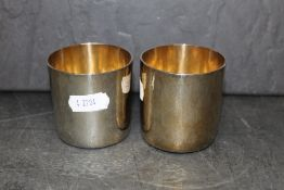 A pair of Elizabeth II 9ct gold toasting cups of simple planished design by RNRG each 6 cm diameter