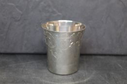 An Elizabeth II silver beaker with flared rim and engraved with leaf and floral ornaments,