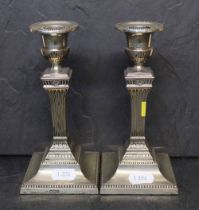 A pair of late Victorian silver pillar candlesticks of reeded column design on square bases,