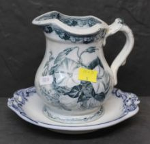 A 19th century blue and white pottery jug, transfer printed with flowers, 15 cm high,