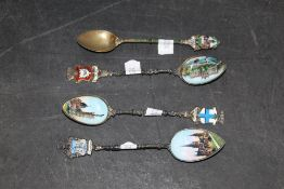 Four early 20th century continental white metal and enamelled souvenir teaspoons respectively for