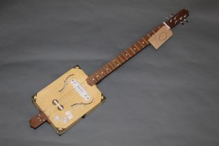 A hand built cigar box electric guitar, 95 cm long with stand for same.