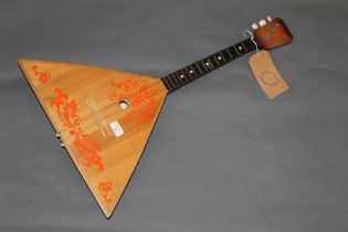 A 20th century Balalaika, the body painted in red with scrolled leaves, 67 cm long,