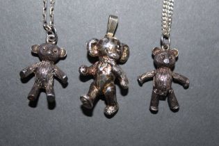 Three teddy bear pendants, two with chains.