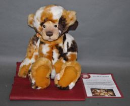 """A soft plush """"Leonie"""" Charlie Bear, CB124915, having a blonde, brown, and white patch fur body,"""