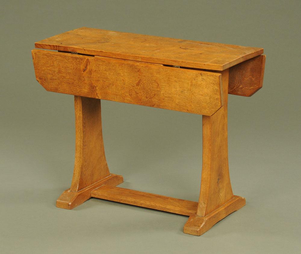 A good quality adzed oak rectangular drop leaf table on trestle end supports,