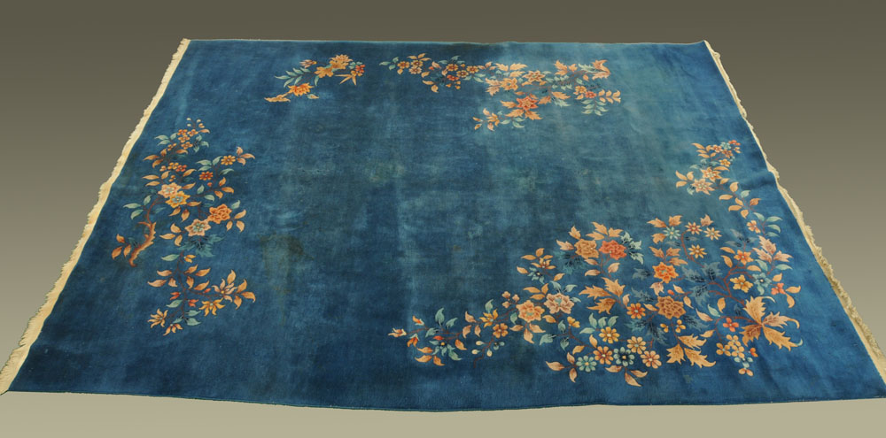 A large Chinese blue ground foliate patterned carpet with fringed ends.
