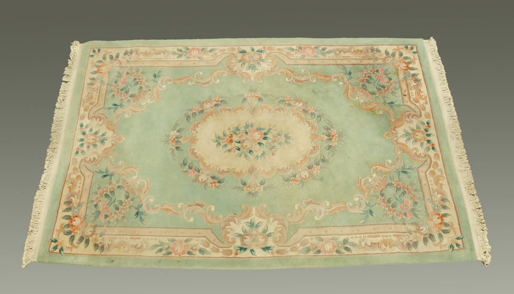 A Chinese woollen carpet, foliate patterned with green and beige ground.