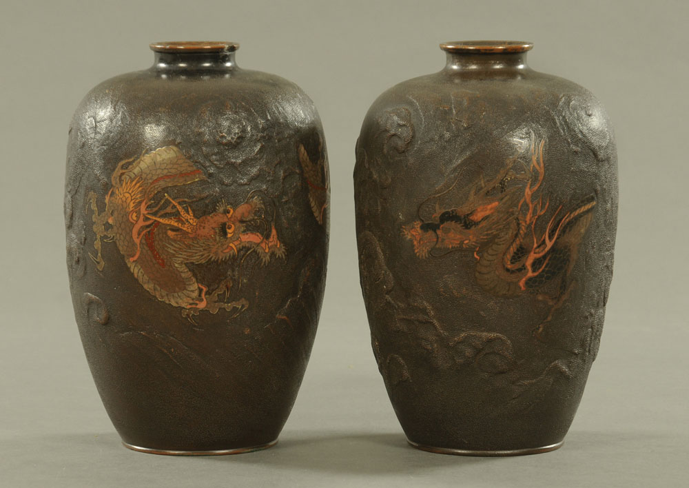 A pair of Japanese bronze vases, decorated with chasing dragons. Height 26 cm.