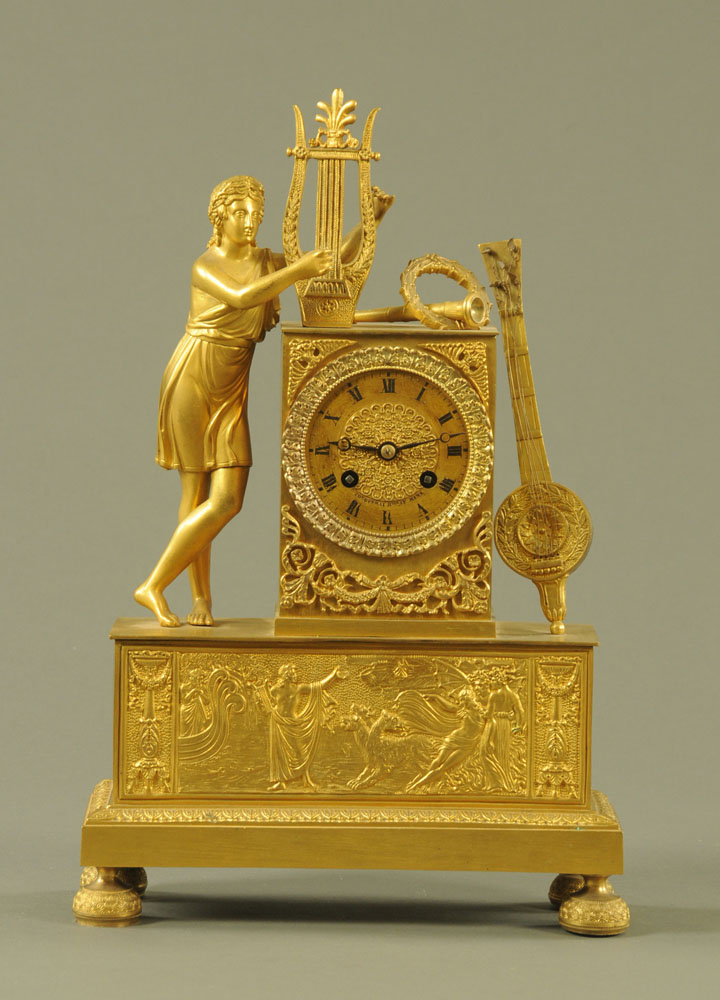 A 19th century gilt metal figural mantle clock, with musical emblem,