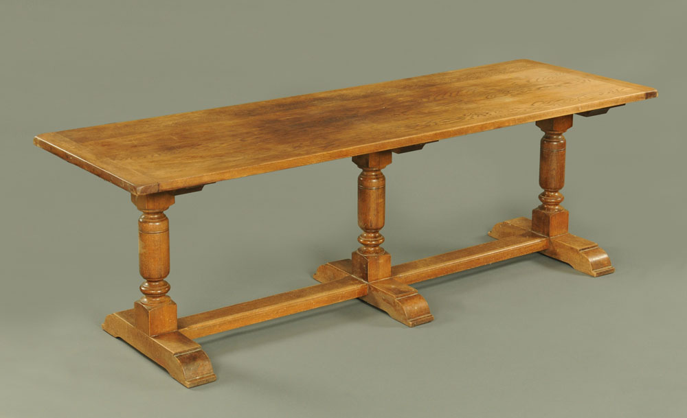 An oak refectory table, with three turned supports, centre stretcher and raised on sledge feet.