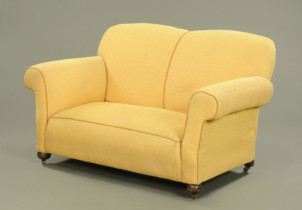 An Edwardian drop end two seat settee, upholstered in yellow cloth on turned front legs and castors.