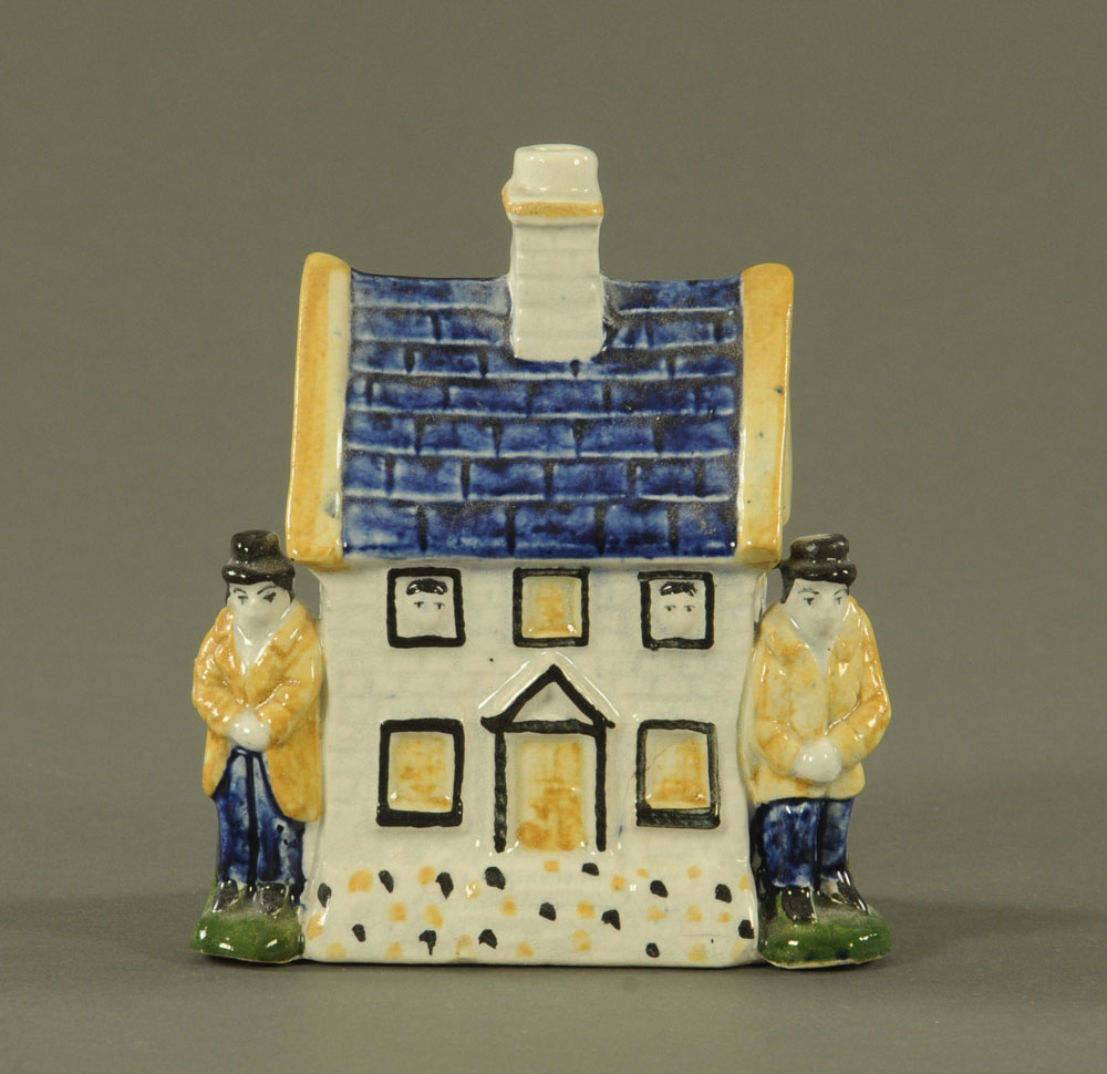 A 19th century Staffordshire pottery money box modelled as a cottage, decorated in muted blue,