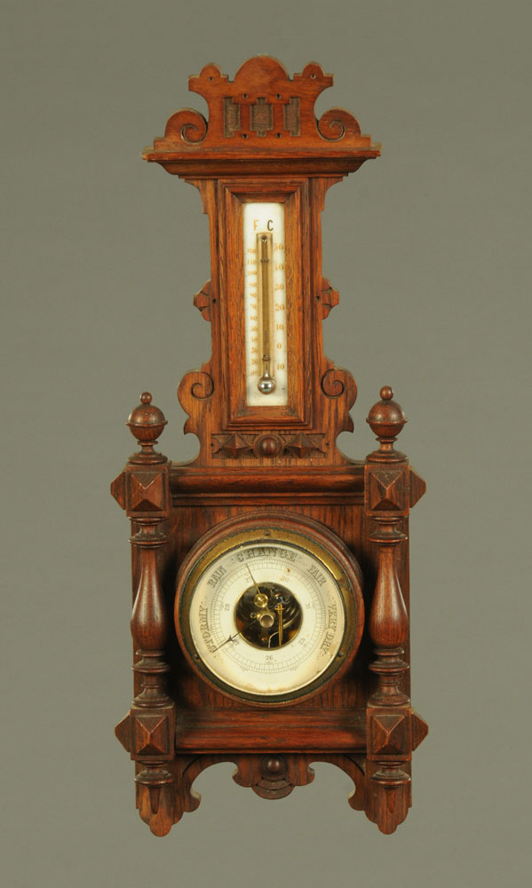 An early 20th century oak aneroid barometer with mercury thermometer. Height 48 cm, width 19 cm.