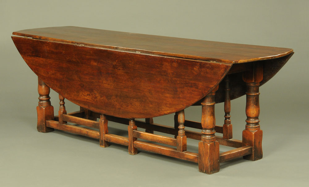 A large oak wake table, twin drop flap with turned supports and double gatelegs with low stretchers.