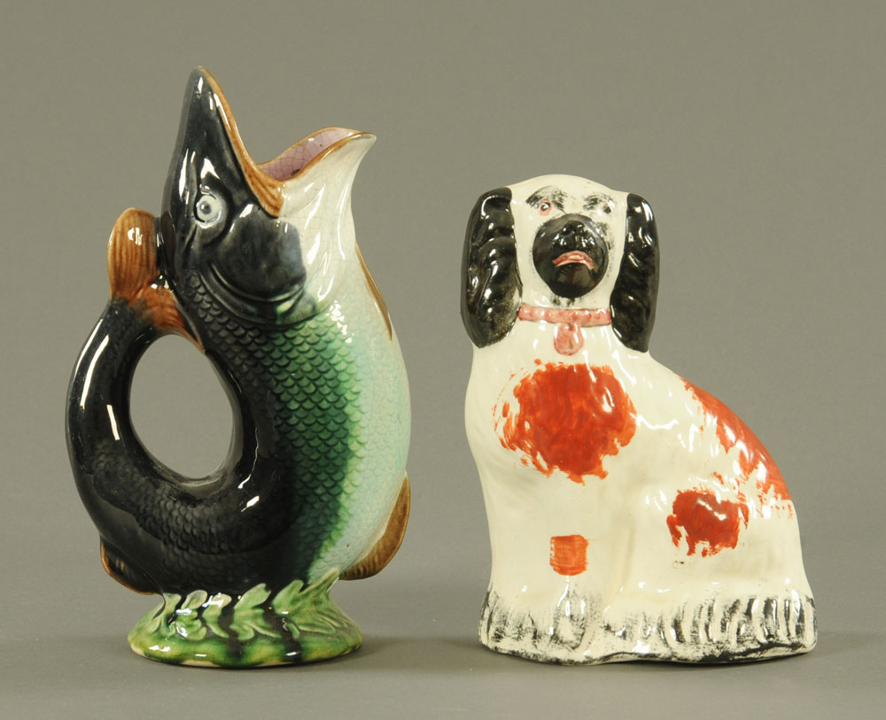 A Staffordshire style pottery spaniel. 22 cm high and a Dartmouth style pottery fish Gluggle jug.