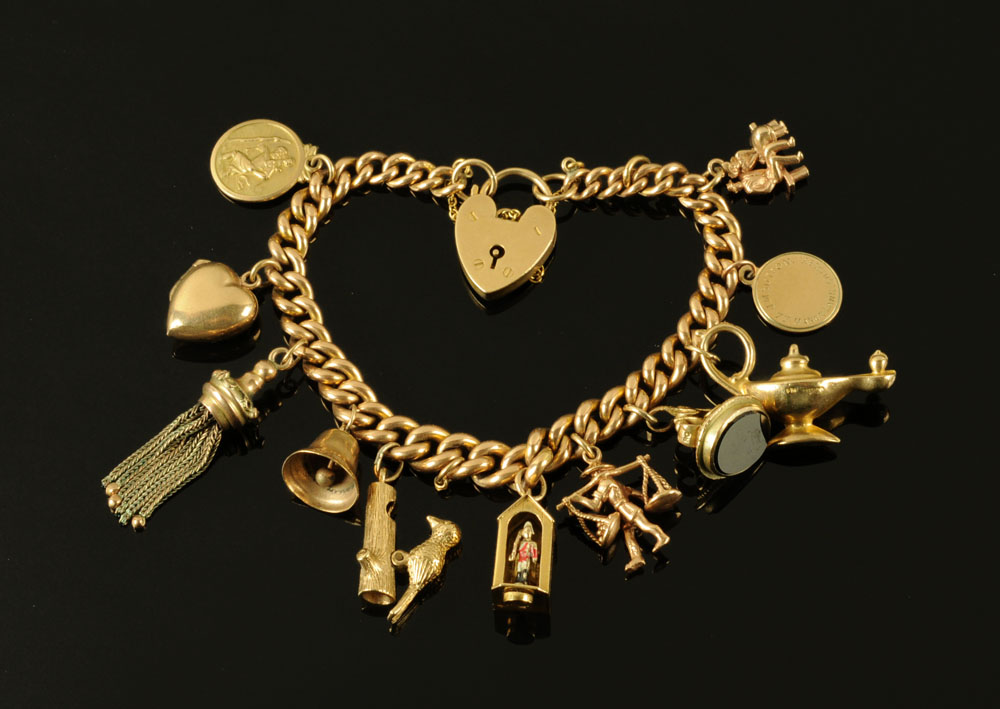 A 9 ct gold charm bracelet, with padlock and ten charms. 45 grams.