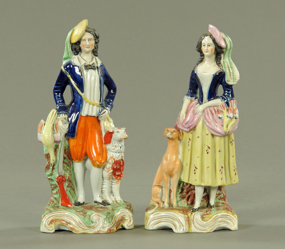 A pair of 19th century Staffordshire figures, huntsman and huntress. Height 27 cm.