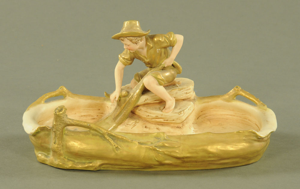 A Royal Dux shallow bowl with seated boy fisherman, pink triangular mark to base. Length 33 cm.