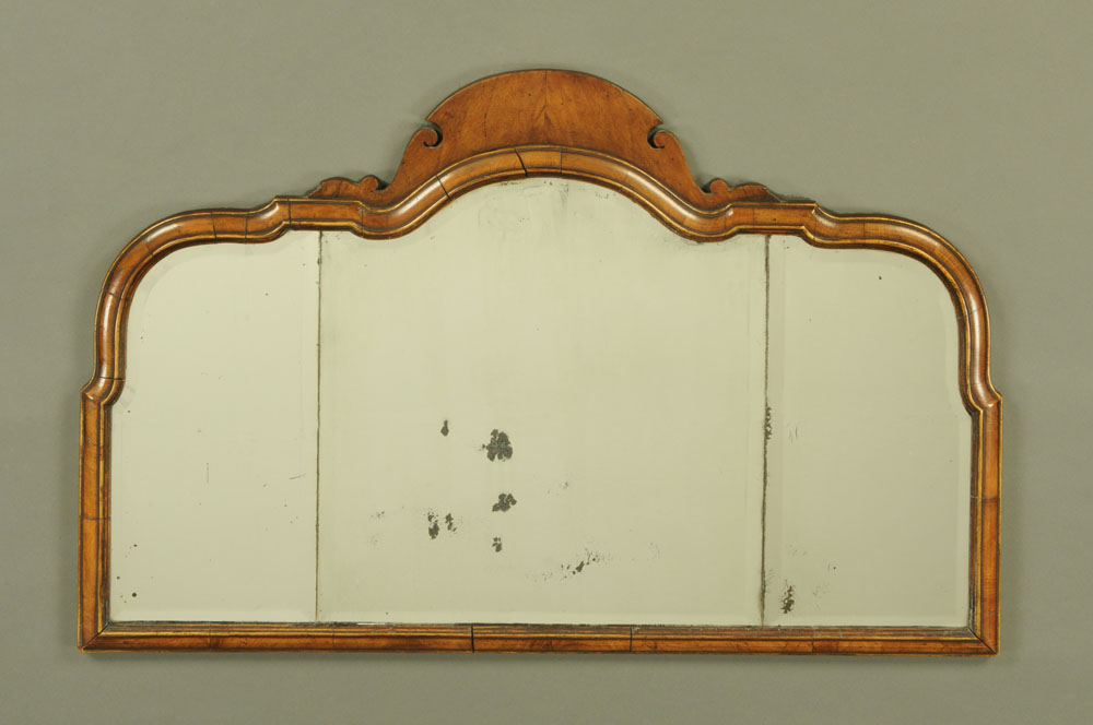 An early 20th century walnut framed Queen Anne style mirror, with three bevelled glass panels.