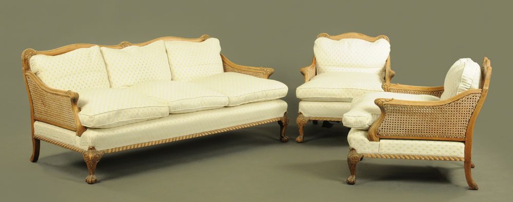 A walnut framed bergere lounge suite, comprising two chairs and settee,
