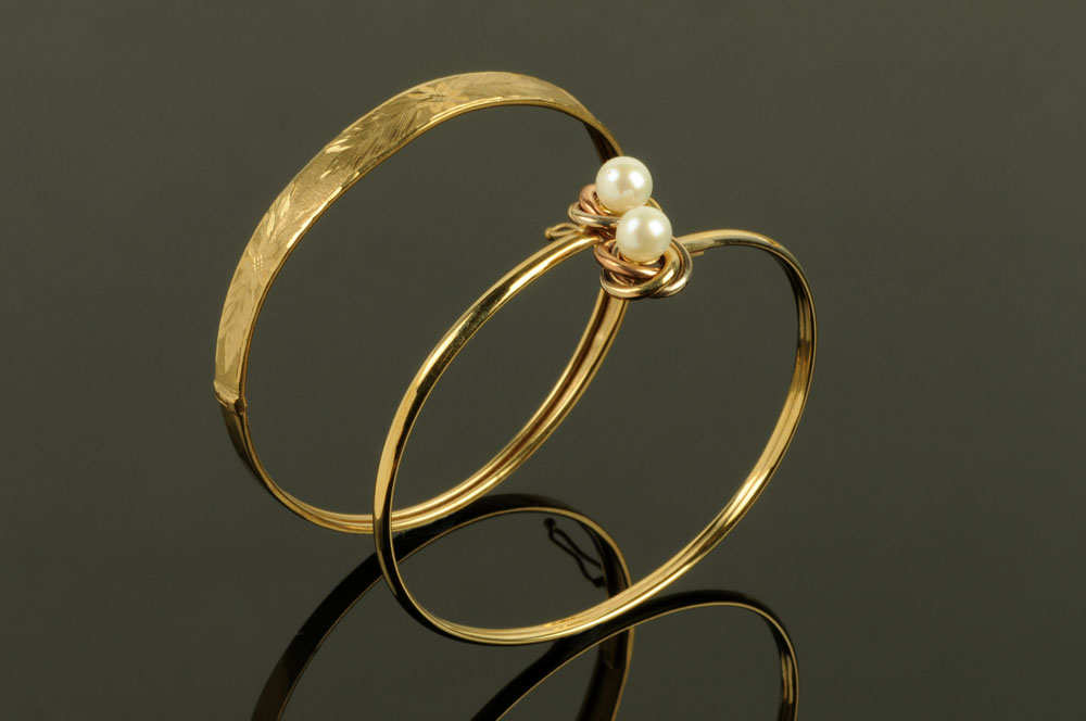 Two 9 ct gold bangles, one with pearl terminals, 10.8 grams gross.
