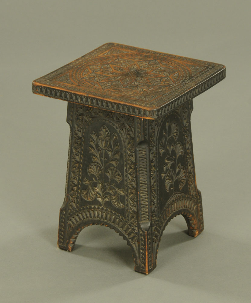 An Eastern carved wooden and ebonised low pedestal, with square top and angled supports.