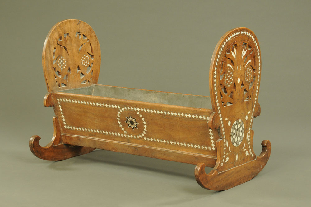 An early 20th century near Eastern mahogany rocking crib, with shaped and pierced ends,