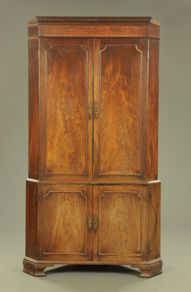 An early 19th century mahogany standing corner cupboard,