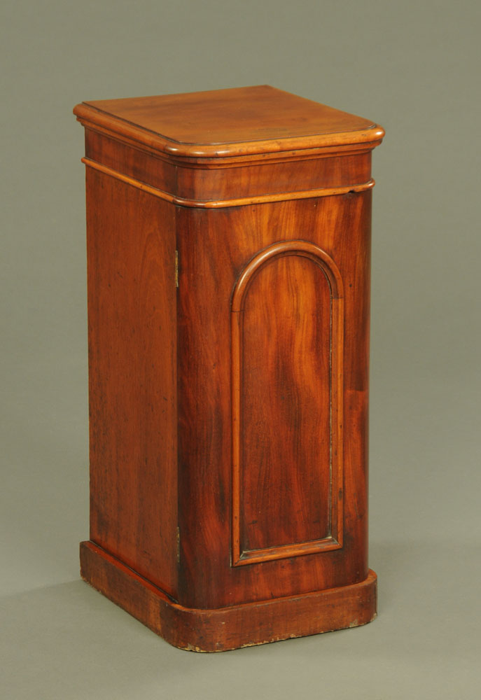 A Victorian mahogany narrow bedside cabinet, with rounded corners panelled door and plinth base.