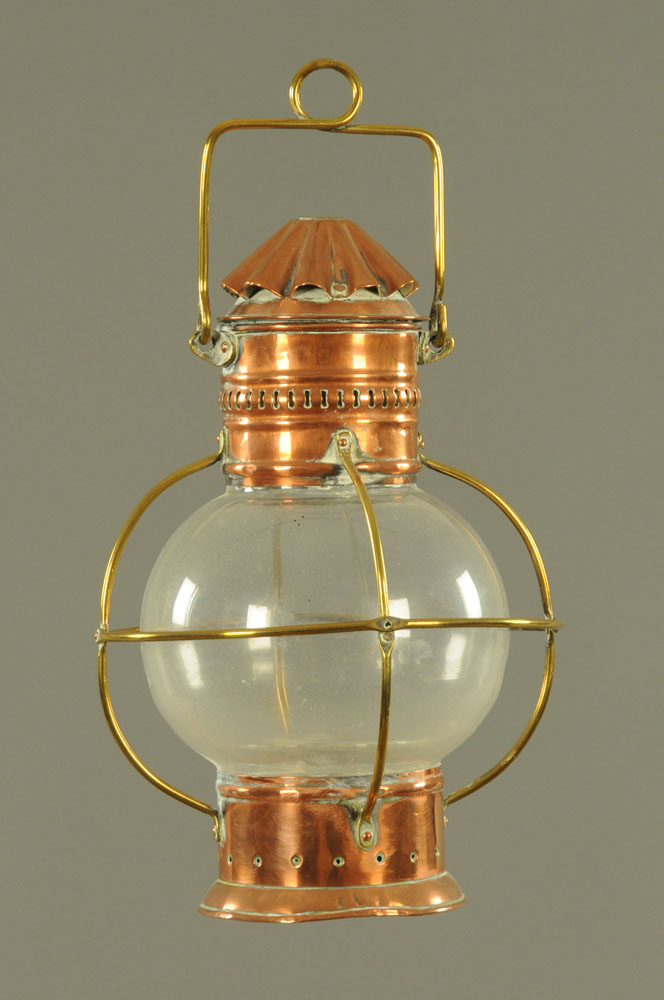 A Victorian copper and brass mounted tilly lamp, with spherical clear glass shade.