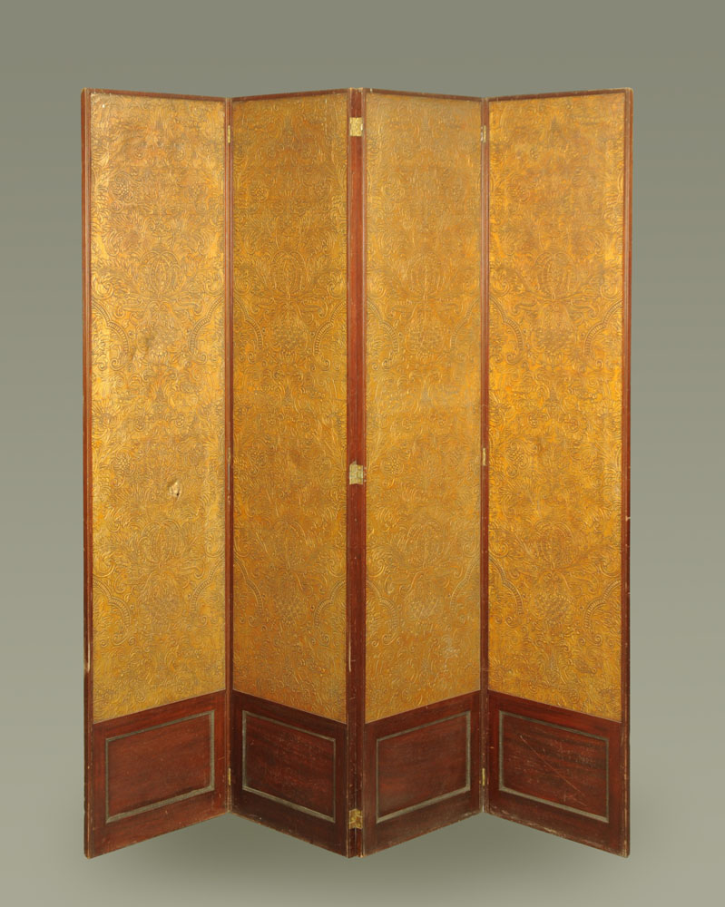 A massive mahogany four fold screen, with gilt embossed cloth panels.