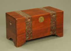A Chinese carved camphorwood trunk, with carved bands and raised on stepped feet.