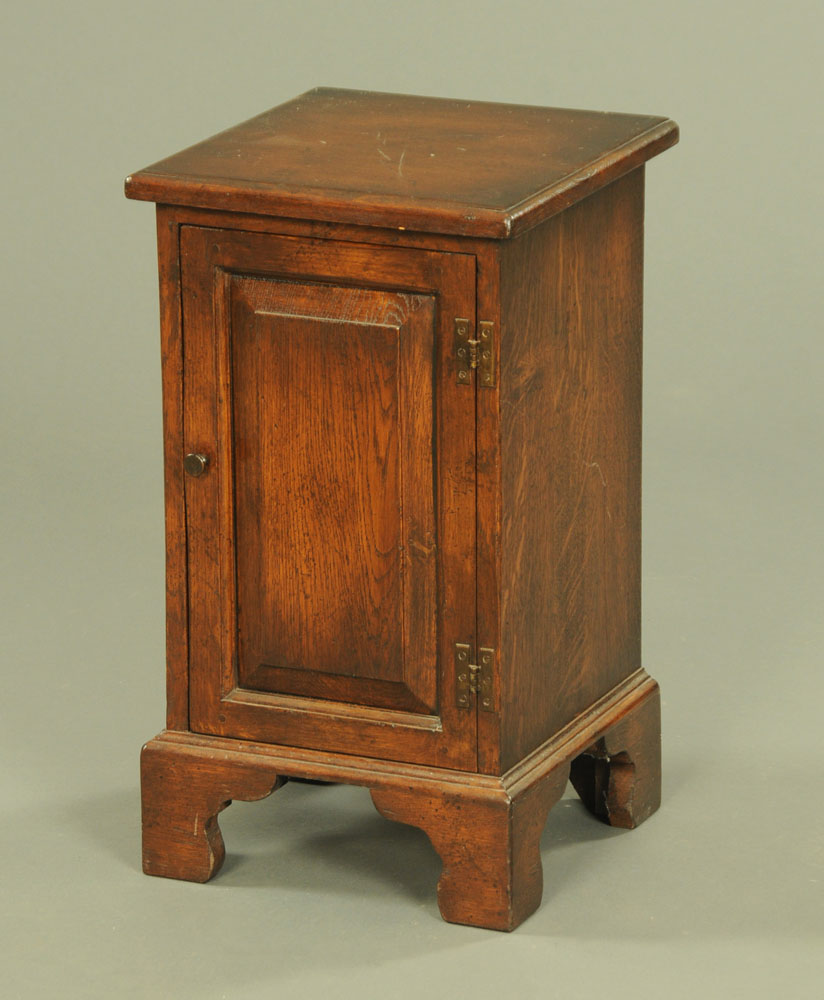 A reproduction oak bedside cabinet, with moulded edge,