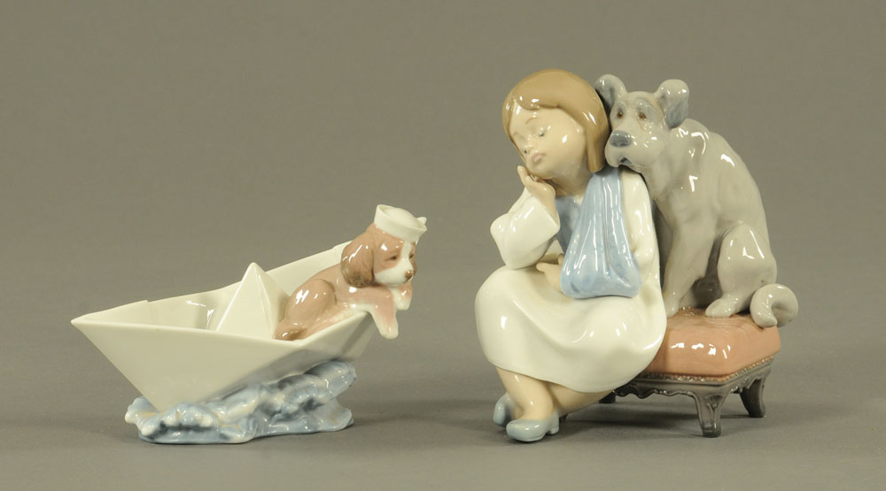 Two Lladro figures, dog in boat and girl with dog. Tallest 16 cm.