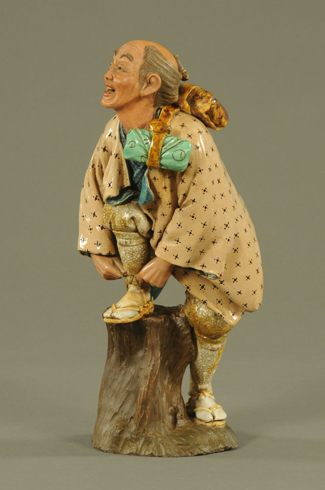 A Japanese ceramic figure of a man tying his sandal. Height 14 cm (see illustration).