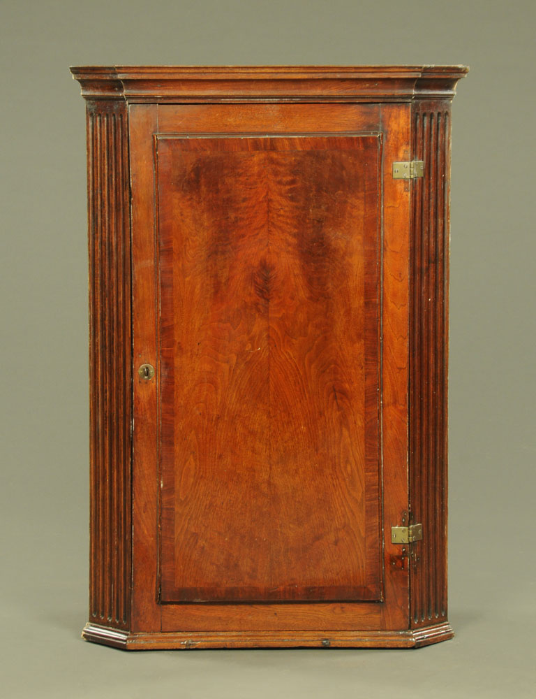 A George III mahogany corner cupboard, with fluted canted corners,