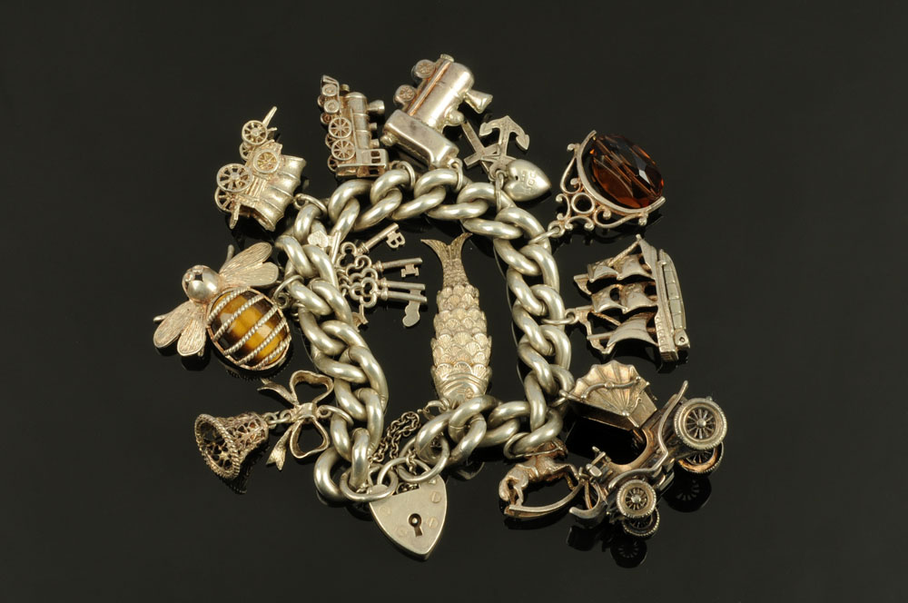 A silver charm bracelet with large quantity of charms, gross weight 108 grams.