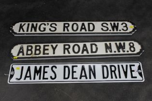 Three road sighs (two wood and one metal) Abbey Road, Kings Road, and James Dean Drive.